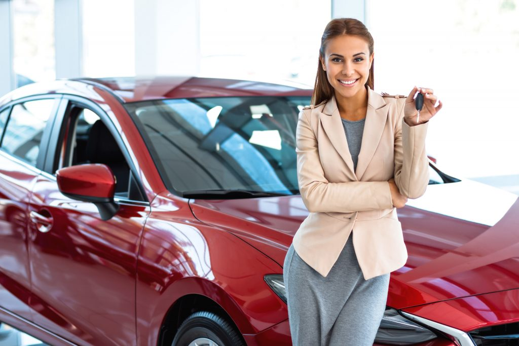 woman showing key to her new car