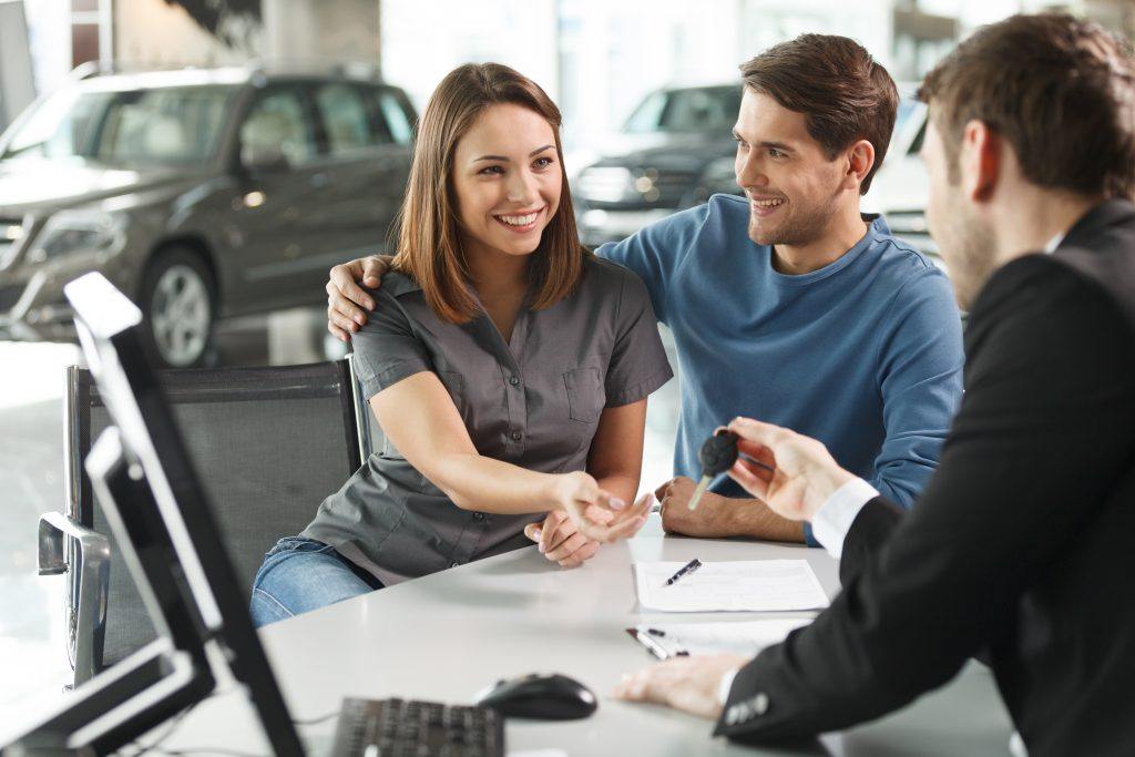 Affordable-Car salesman giving the key of the new car to the young attractive owners – her dreams come true
