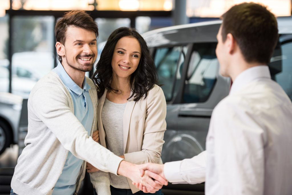 Young couple grateful sales manager for advice in auto salon